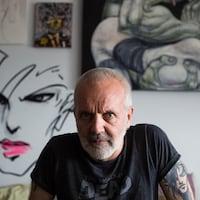 L'artiste Zilon devant quelques peintures et graffitis