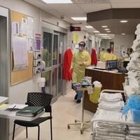 Une allée d'hôpital avec 5 chambres qui ferment par des portes automatiques. Un poste où discute une équipe de soins.