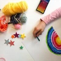 Bricolage arc-en-ciel avec des crayons de pastel, de la laine et des étoiles