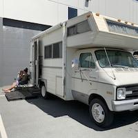 Jordan Duguay et Gabrielle Mantha assis à côté de leur caravane motorisée.