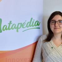 Une jeune femme pose devant la bannière de La Matapédia