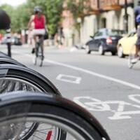 Des BIXI stationnés dans une rue avec des cyclistes à l'arrière.