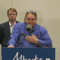 Le chef Douglas Beaverbones se tient debout derrière un podium, la main sur la poitrine. Derrière lui se trouve le ministre de la santé Tyler Shandro.