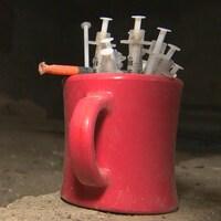 Des seringues usagées dans une tasse posée au sol.