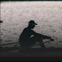 Un rameur s'entraîne sur un plan d'eau.