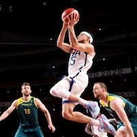 Un joueur de basketball saute et tente un tir sous le regard de trois adversaires.