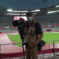 Bernard Brault tient un appareil photo et un trépied dans le stade olympique de Tokyo.