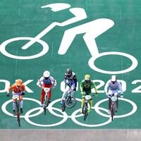 Six athlètes de BMX saute sur une première bosse après la descente de départ lors d'une épreuve olympique. Le logo géant de la discipline avec l'inscription Tokyo 2020 apparaît en arrière.