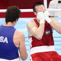 L'Ouzbek Bakhodir Jalolov, émotif, avec les mains devant son visage et Richard Torrez Jr qui le regarde, debout.