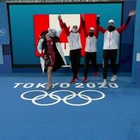 Quatre femmes se tiennent les mains en portant un survêtement aux couleurs du Canada.
