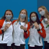 Arborant un masque gris et une combinaison aux couleurs du Canada, les Canadiennes Penny Oleksiak, Kylie Masse, Maggie Mac Neil et Sydney Pickrem tiennent fièrement leur médaille de bronze sur le podium.