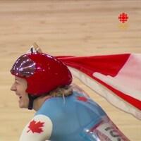 La cycliste canadienne Kelsey Mitchell soulève le drapeau canadien après avoir remporté la finale du sprint en cyclisme sur piste.