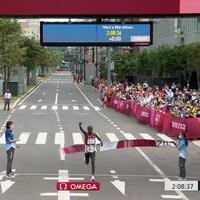 Un homme franchit le fil d'arrivée d'une course olympique.