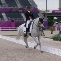Une femme est sur un cheval trottant lors d'une compétition. Les gradins arrière sont vides.