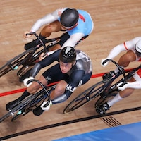 Le Canadien Hugo Barrette est sur son vélo accompagné de ses adversaires Sam Webster de la Nouvelle-Zélande et Patryk Rajkowski de la Pologne.