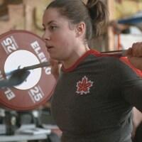 Une haltérophile est concentrée pendant l'entraînement.