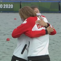 Deux coéquipières s'enlacent après leur médaille en canoë sprint.