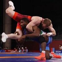 Un lutteur soulève son adversaire pendant un combat.