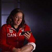 L'haltérophile Maude Charron lit des messages sur un téléphone.