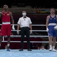 Un boxeur célèbre sa victoire sur le ring face à son adversaire dépité. Un arbitre est placé entre eux.
