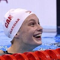 La nageuse canadienne Penny Oleksiak affiche un grand sourire dans la piscine olympique.