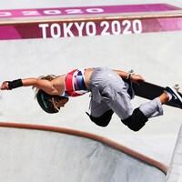 L'athlète effectue une figure aérienne avec sa planche à roulette dans le parc olympique.