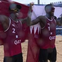 Avec un grand sourire et des lunettes de soleil, les deux joueurs de volleyball de plage du Qatar posent fièrement avec chacun leur drapeau de leur pays, qu'ils tiennent à fièrement à bout de bras.