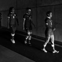 Les joueuses de rugby marchent dans un tunnel entre le terrain et le vestiaire.