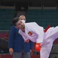 Un karatéka exécute un coup de pied qui atteint son adversaire au visage.