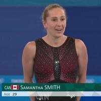 D'un air étonné, la Canadienne Samantha Smith tient ses mains derrière elle avec sa combinaison de gymnaste aux couleurs du Canada, en attente de son résultat lors de l'épreuve de gymnaste.