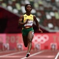 Une coureuse en jaune et en vert sur une piste d'athlétisme