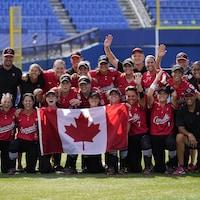Les joueuses, les entraîneurs et le personnel de l'équipe posent fièrement avec un drapeau canadien au centre du terrain après leur victoire.