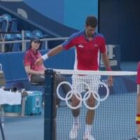 Un joueur de tennis regarde sa raquette brisée sur le sol.