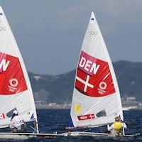 Sarah Douglas de l'équipe du Canada et Anne-Marie Rindom de l'équipe du Danemark sont sur leur voilier en pleine action. La Canadienne se retrouve à être derrière la Danoise.