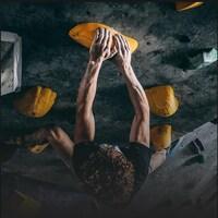 Un athlète escalade un mur.