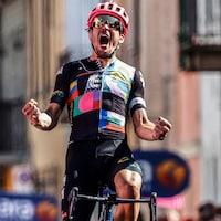 Le cycliste brandit les deux poings, tout en criant sa joie au terme de sa victoire.