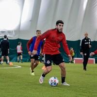Un joueur de soccer lors d'un match disputé sur une surface synthétique à l'intérieur.