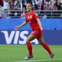Elle étend les bras pour célébrer un but.