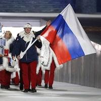 Il avance dans le stade devant ses coéquipiers russe et tient le drapeau dans ses mains.