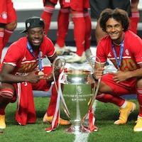 Deux joueurs de soccer du Bayern de Munich prennent la pose accroupis près du trophée.