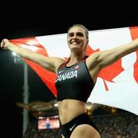 Alysha Newman, tout sourire, tient fièrement le drapeau canadien après avoir gagné l'or au saut à la perche des Jeux du Commonwealth