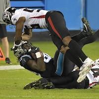 Deux joueurs de football plaquent un joueur adverse au sol.