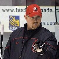 Un homme avec une casquette au logo d'Hockey Canada et un gant de hockey