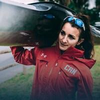 Andréanne Langlois transporte son kayak sur une épaule.