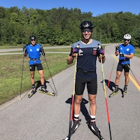 Trois skieurs posent pour la caméra dans un parc avec leurs skis à roulettes.
