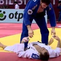 Un judoka blessé étendu au sol. Son adversaire tente de l'aider
