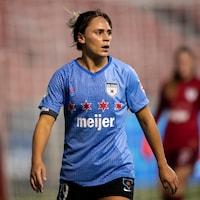 Une joueuse de soccer marche sur le terrain pendant un match
