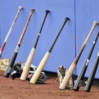 Des bâtons et des gants de baseball posés sur le sol.