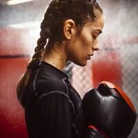 Une femme dans un gym avec des gants de boxe. Elle semble se concentrer.