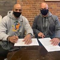 Oscar Rivas (à gauche) et son gérant Stéphane Lépine signent le contrat pour le combat de championnat du monde contre Bryant Jennings